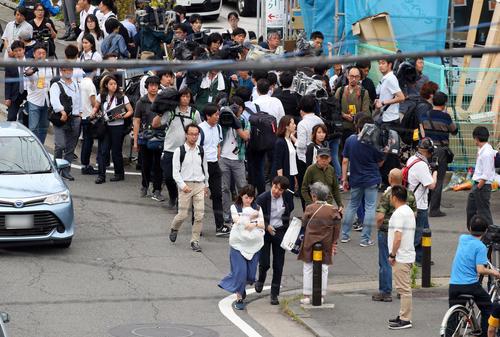 事件現場の献花し報道陣の視線を受けながら足場やに引き揚げる女性(撮影・垰建太)