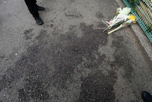 献花された路肩には、洗い流された血だまりの跡が生々しく残る(撮影・河田真司)