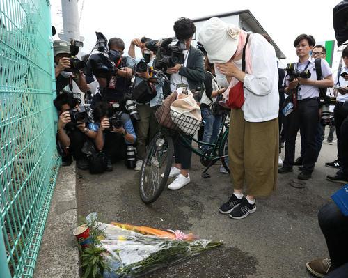 事件現場で亡くなった人に献花し手を合わせる女性(撮影・河田真司)
