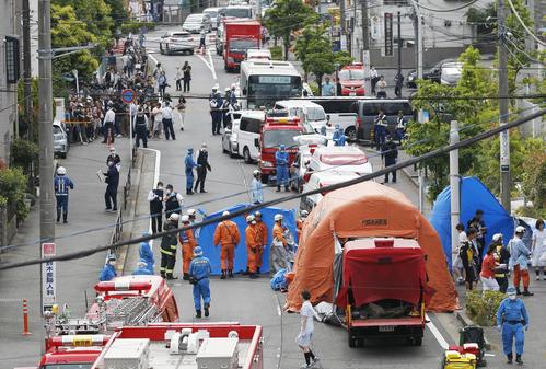 小学生を含む複数の人が刺された現場で救助活動をする消防隊員ら。中央上は通学バス(共同)