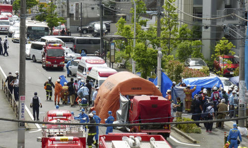 小学生を含む複数の人が刺された現場で救助活動をする消防隊員ら。上左は通学バス(共同)