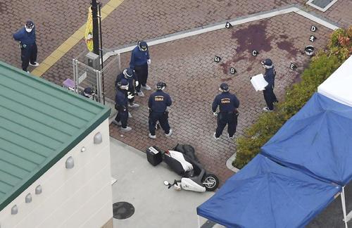 警察官が刺され拳銃が奪われる事件があった千里山交番(左下)周辺を調べる捜査員(共同)
