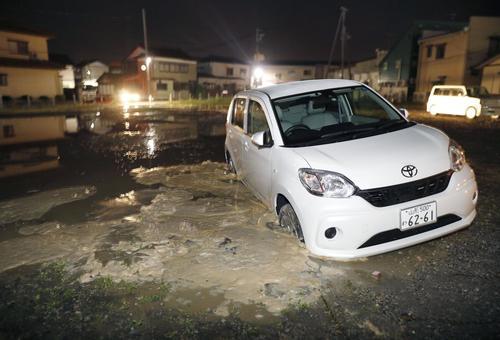 山形県鶴岡市内の駐車場で、地面に沈み込んだ車(共同)
