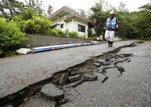 亀裂が入った道路。ブロック塀も崩れていた=19日午前8時47分、山形県鶴岡市(共同)