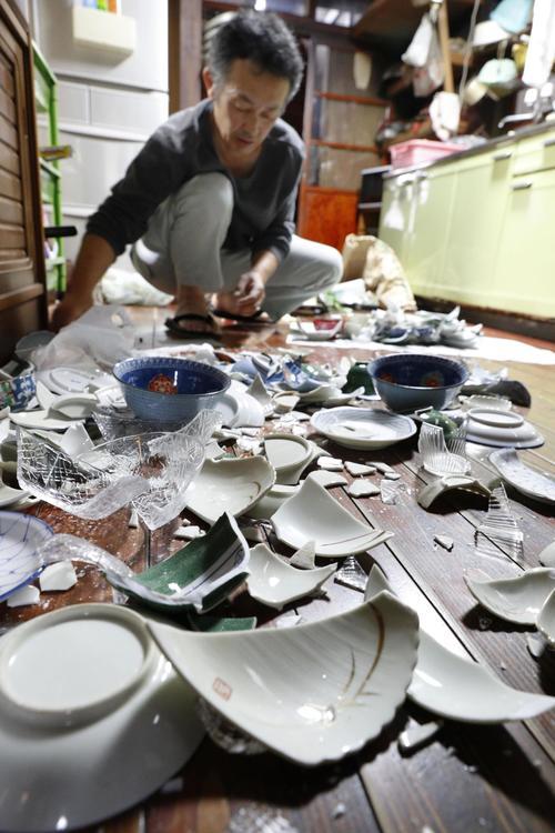 地震で床に落ち、割れて散乱した食器=19日午前5時47分、新潟県村上市府屋地区(共同)