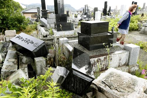 地震で墓石が倒れた墓地=19日午前6時18分、新潟県村上市(共同)
