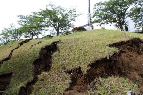 強い地震で崩れた新潟県村上市の山北総合体育館敷地内の斜面=19日午前6時45分(共同)