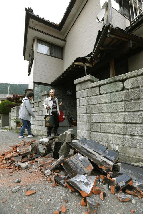 住宅の玄関前に積まれた屋根から落ちた瓦=19日午前5時22分、山形県鶴岡市(共同)