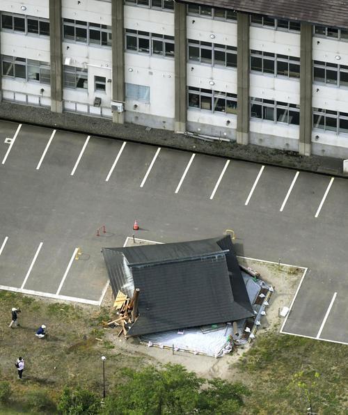 地震により倒壊した山形県鶴岡市立大泉小の相撲場(手前)=19日午前7時36分(共同)