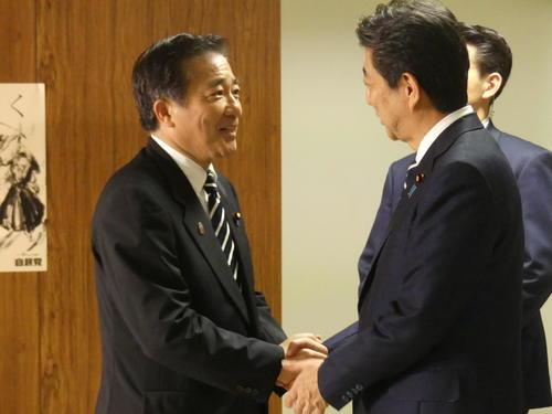 自民党本部を訪れ、安倍晋三首相(右)と握手する長島昭久氏