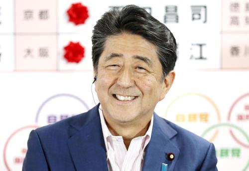 自民党本部の開票センターで、テレビ局のインタビューに笑顔で答える安倍首相(共同)