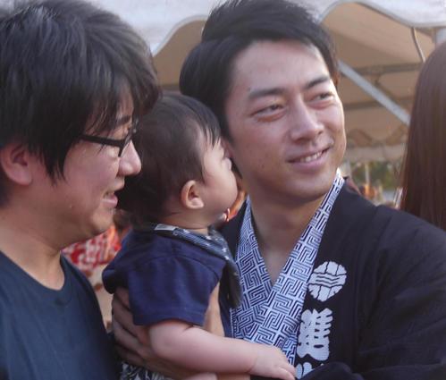 地元の夏祭り会場で、赤ちゃんを抱いて写真撮影に応じる小泉進次郎氏