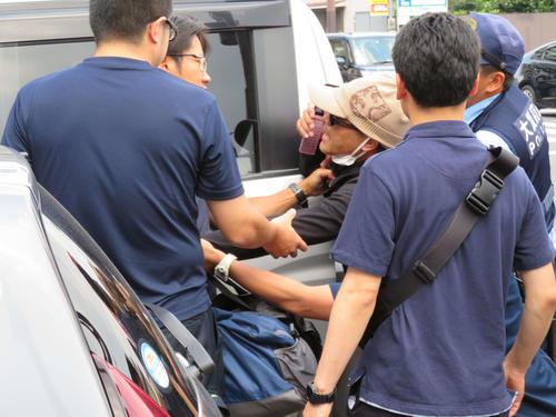 車に乗せられるのを必死に抵抗する宮崎文夫容疑者の手にはガラケーがあった(撮影・佐藤勝亮)