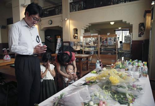 京都アニメーションの作品「けいおん!」の舞台のモデルとされる滋賀県豊郷町の豊郷小旧校舎に設置された献花台を訪れ、手を合わせる親子(共同)