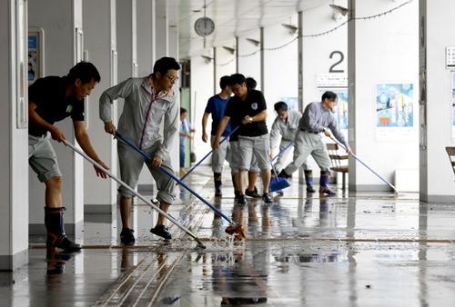 大雨で浸水したJR佐賀駅で、水をかき出す人たち(共同)