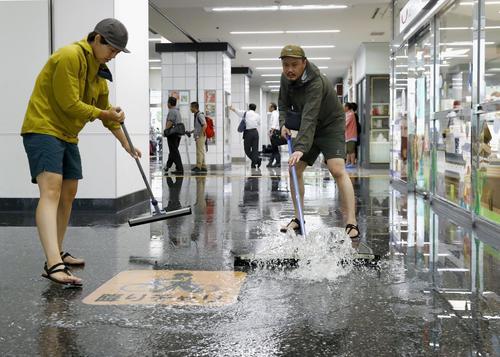 大雨で浸水したJR佐賀駅で、水をかき出す近隣の住民ら(共同)