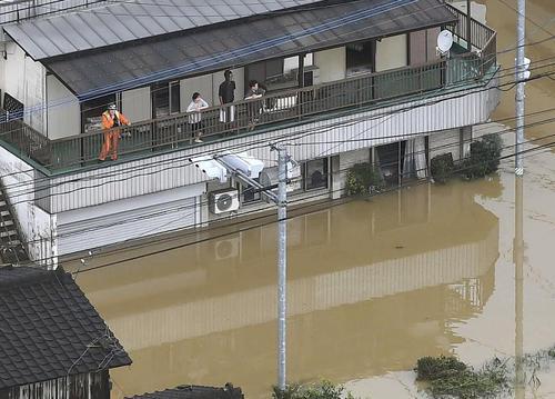 大雨で浸水した佐賀県武雄市で、住宅の2階に避難した市民ら(共同)