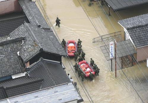 大雨で浸水した佐賀県武雄市で、ボートを使い救出に向かう自衛隊員(共同)