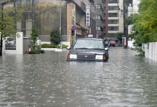 大雨の影響で道路が冠水し、立ち往生したタクシー(共同)