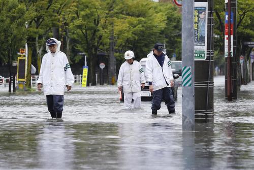 大雨で冠水した道路を見回る警察官(共同)