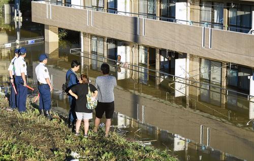 13日午前6時41分・川崎市 台風19号で浸水被害のあったマンションの脇で立ち尽くす近隣住民ら。1階部分で住民が死亡した