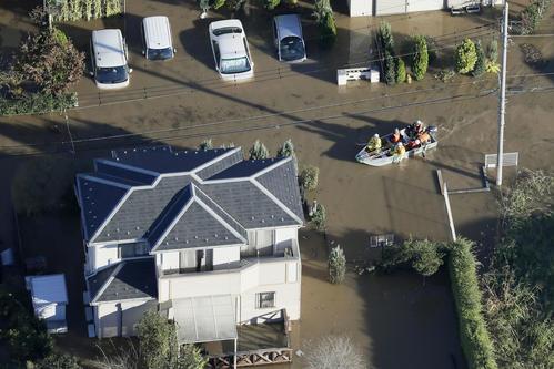13日午前7時5分、埼玉県坂戸市 台風19号の大雨で冠水した市街地をボートで進む救急隊員ら(共同)