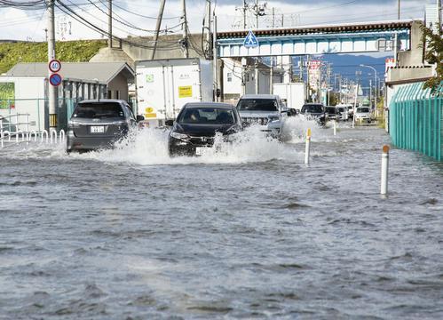 13日午前8時29分、宮城県柴田町 冠水し川のようになった道路を進む車(共同)