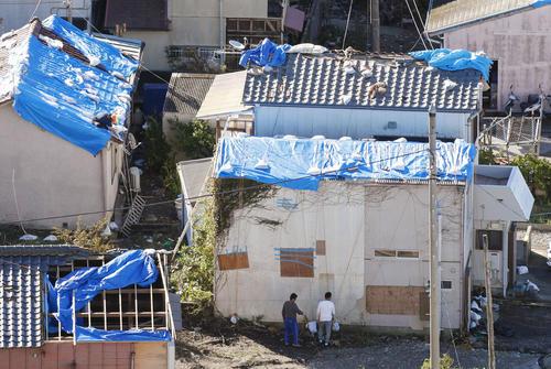 13日午前8時28分、千葉県鋸南町 台風19号の暴風雨ではがれ落ちた屋根のブルーシート。先の台風15号で受けたとみられる被害が今も残る(共同)