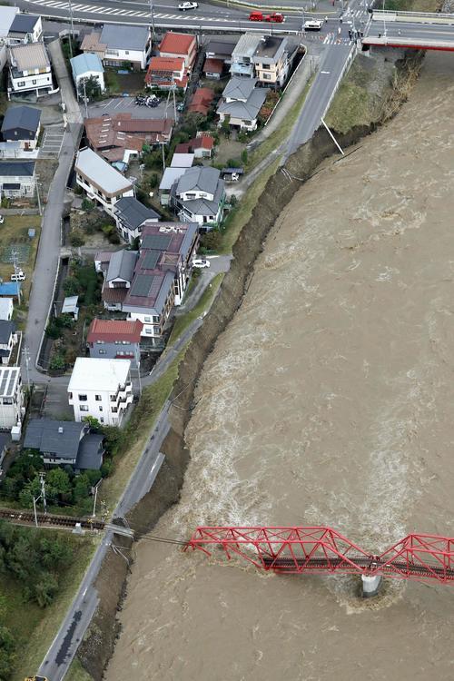 13日午前8時39分、長野県上田市 台風19号による千曲川の増水でえぐり取られた道路。右下は崩落した上田電鉄別所線の橋(共同)