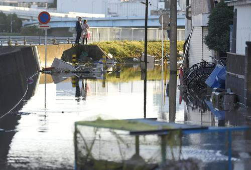 13日午前6時15分、川崎市 台風19号の影響で冠水した道路脇で立ち尽くす人(共同)