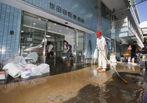 13日午前7時58分、東京都世田谷区 浸水した世田谷記念病院で掃除をする人たち(共同)