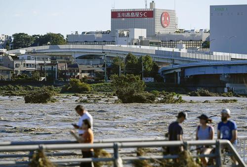 13日午前7時48分 台風19号による大雨で増水し濁流となった多摩川。手前側は神奈川県川崎市、対岸は東京都世田谷区(共同)
