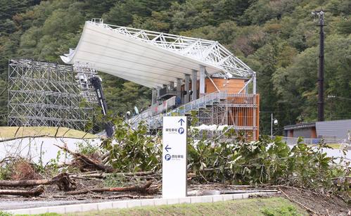 13日 台風の影響でナミビア対カナダ戦が中止となった釜石鵜住居復興スタジアム(奥)の駐車場には、山の斜面から木が崩れ落ちていた(撮影・野上伸悟)