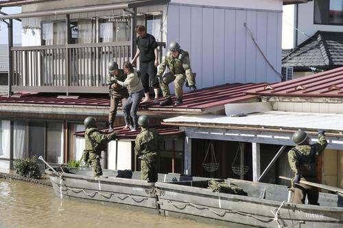 13日午後1時10分、宮城県角田市 台風19号の影響で浸水した家屋から自衛隊員に救出される女性ら(共同)