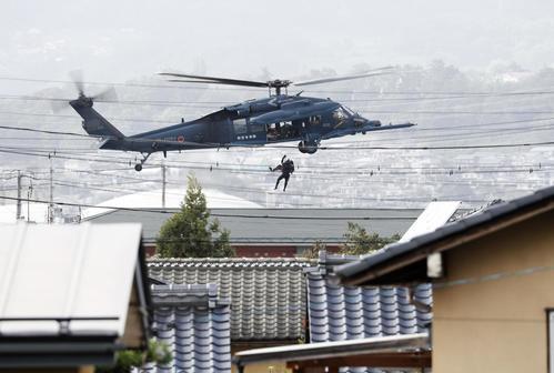 13日午後1時26分 台風19号による大雨で千曲川が決壊した長野市穂保で、ヘリコプターで救助される住民(共同)
