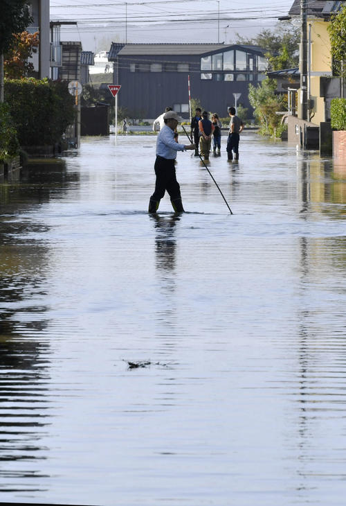 13日午後3時17分 台風19号の影響で冠水した道路を歩く人(共同)