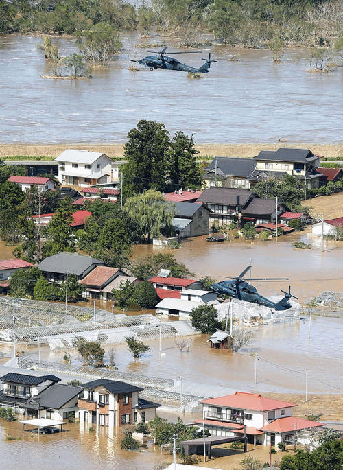 13日午前11時17分、宮城県丸森町 台風19号の影響で浸水した市街地で、救助活動にあたるヘリコプター(共同)