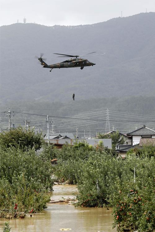 13日午後0時34分 台風19号による大雨で千曲川が決壊した長野市穂保で、ヘリコプターで救助される住民(共同)