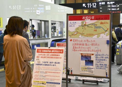 13日午前11時45分 台風19号による大雨の影響で北陸新幹線の車両基地が水没し、JR富山駅の改札口に掲示された東京-富山間の運休の案内