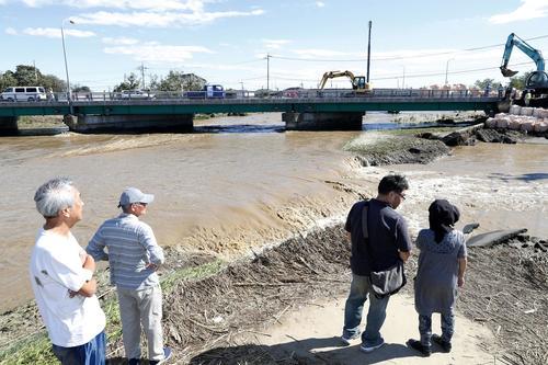 13日午後0時46分、栃木県佐野市赤坂町 秋山川の堤防が決壊し、市街地に流れ込む濁流(共同)
