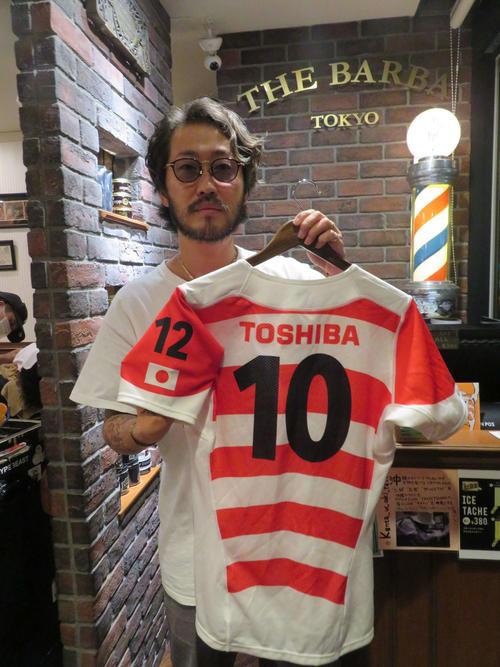 平尾誠二さんの追悼試合となったアルゼンチン戦でSO田村優が着用したユニホームを手に、気合を入れる「THE BARBA TOKYO」オーナーのTOMさん(撮影・村上幸将)