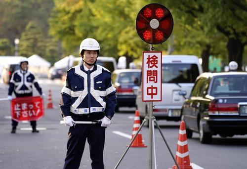 天皇陛下の即位を祝うパレード「祝賀御列の儀」を控え、皇居近くで検問する警察官(共同)