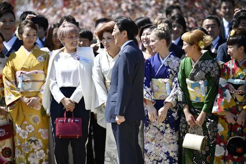 「桜を見る会」での招待客と笑顔の安倍首相(中央)(共同)
