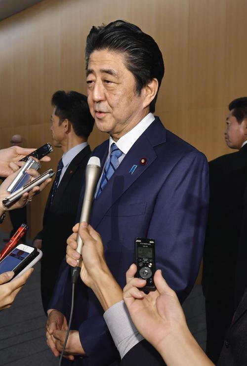 「桜を見る会」の中止発表について、記者団に話す安倍首相(共同)