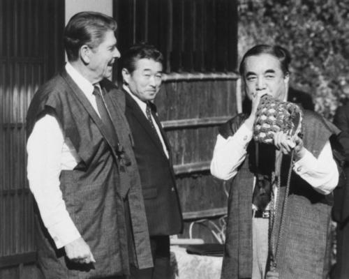 1983年11月、レーガン米大統領(左)にほら貝を吹いてみせる中曽根康弘首相(共同)