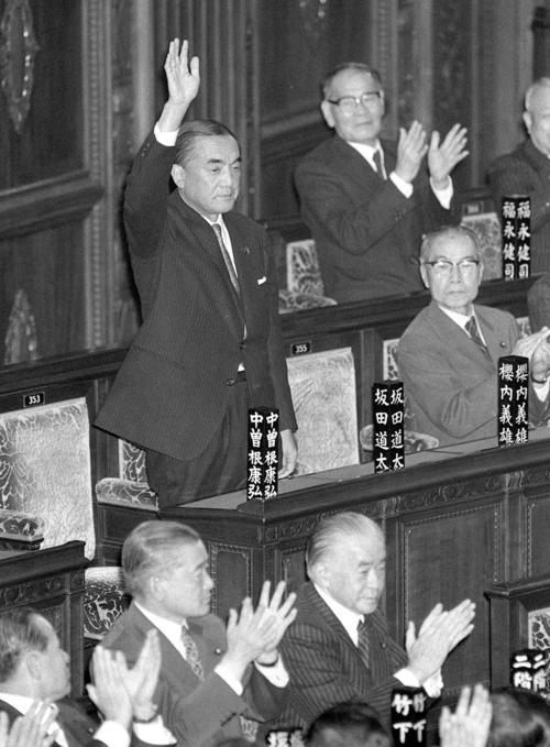 1982年11月、衆院本会議で首相に指名され、手を挙げて応える中曽根康弘氏(共同)