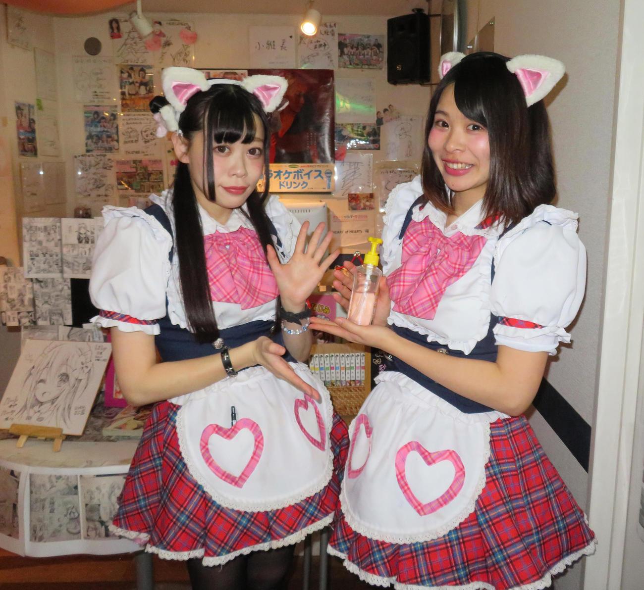 東京都秋葉原のメイド喫茶「ハートオブハーツ」メイドの、ちゃっぴーさん(右)ともちさんは、笑顔で除菌ジェルを持ち写真に納まる(撮影・佐藤勝亮)