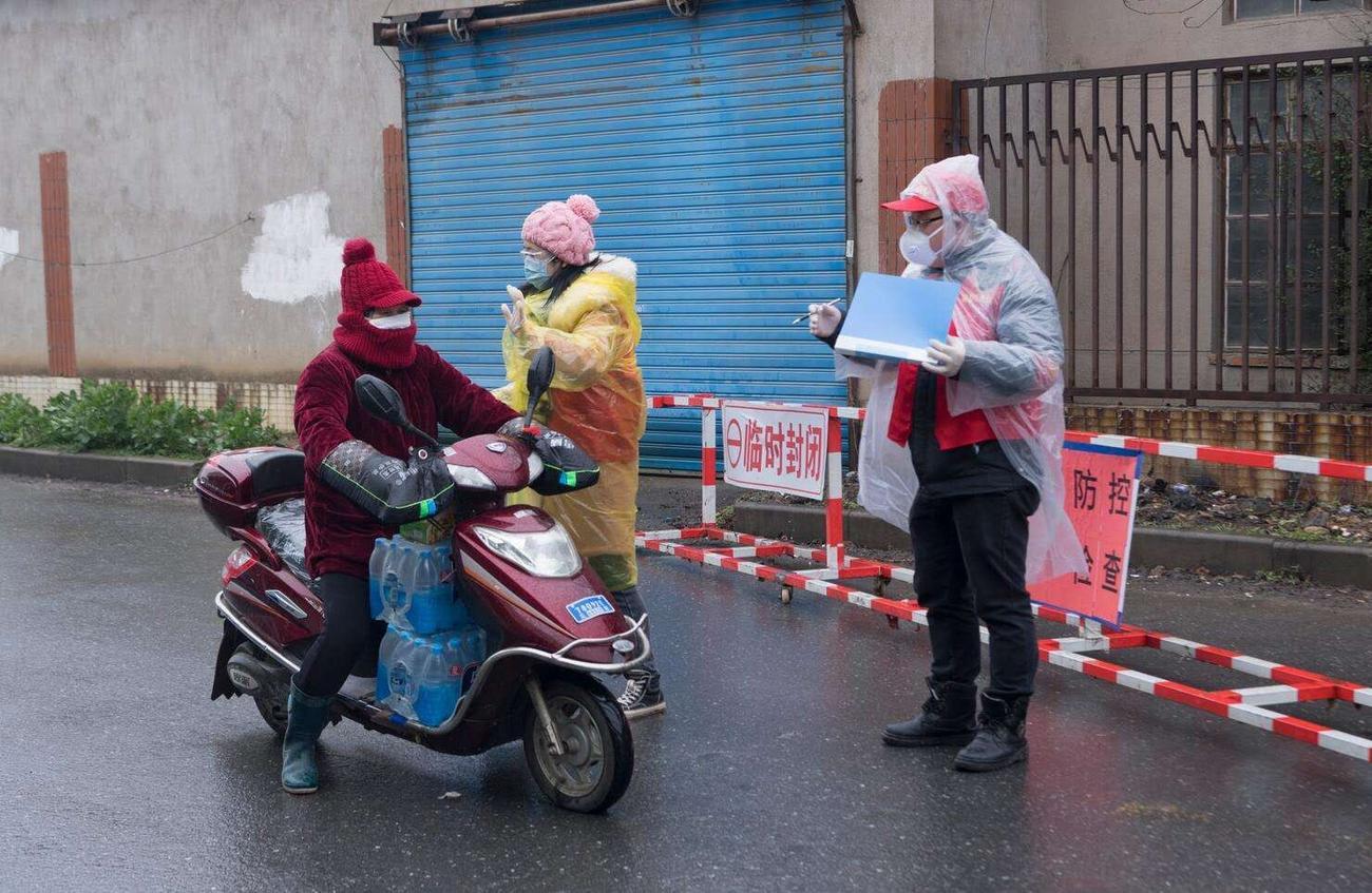 江蘇省無錫市でバイクで走行する人に聞き取りをする担当者(関係者提供)