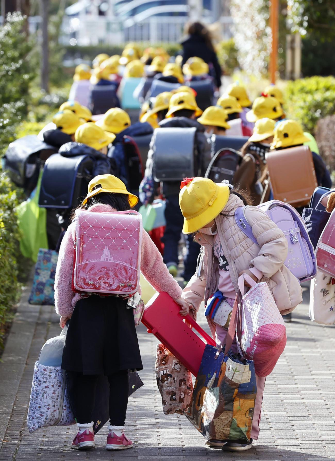 新型コロナウイルスの感染拡大による政府の一斉休校要請で、急きょ学年最後の日となり、たくさんの荷物を手に下校する児童(共同)