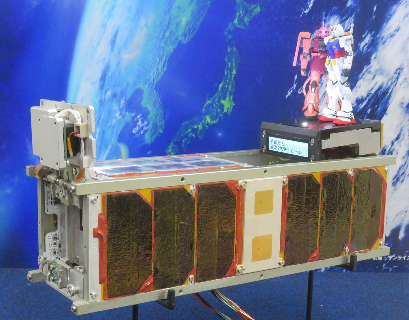 超小型衛星「G-SATELLITE」と、搭載された「ガンダム」と「シャア専用ザク」の模型(2019年12月3日)